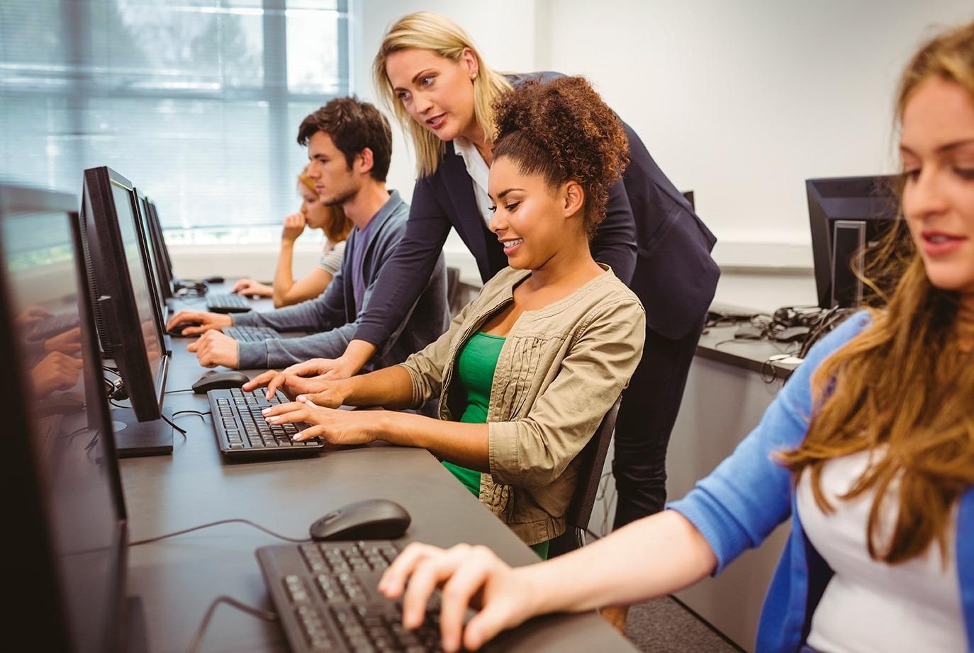 Grupo de estudiantes con una maestro trabajando con computadoras