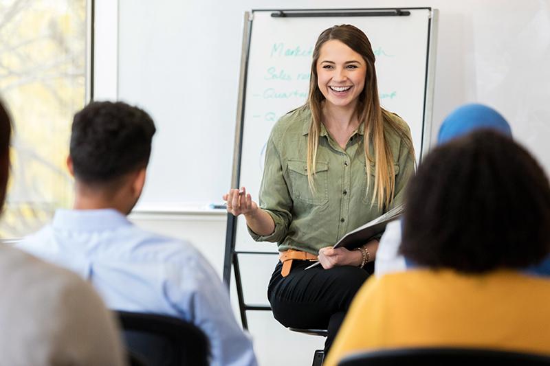 Profesora dando clase frente a un grupo de alumnos